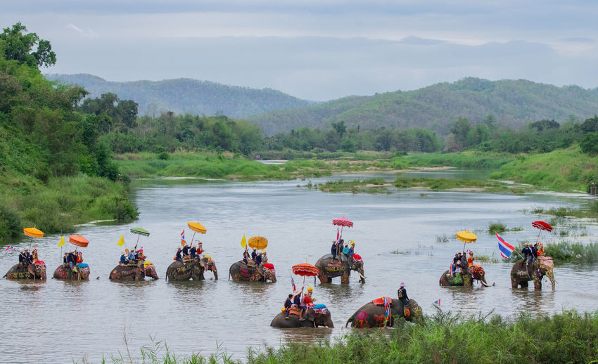 People riding elephant in lake