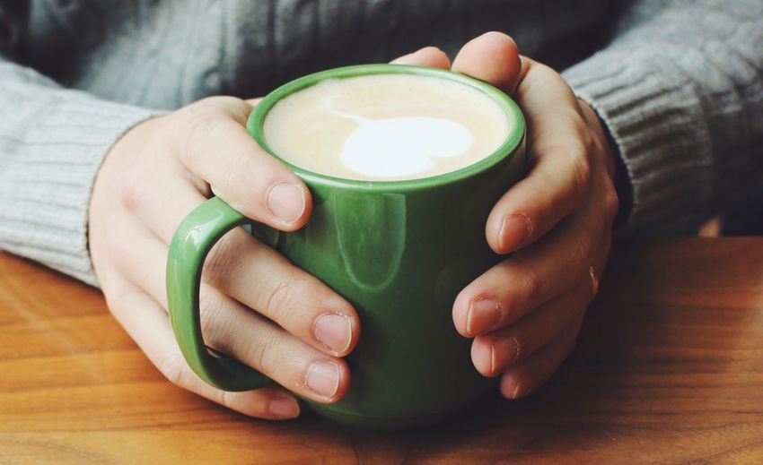 Close-up of hands holding coffee cup on table