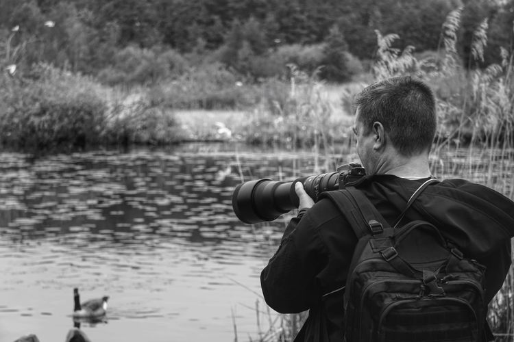 Rear view of man photographing while standing by lake