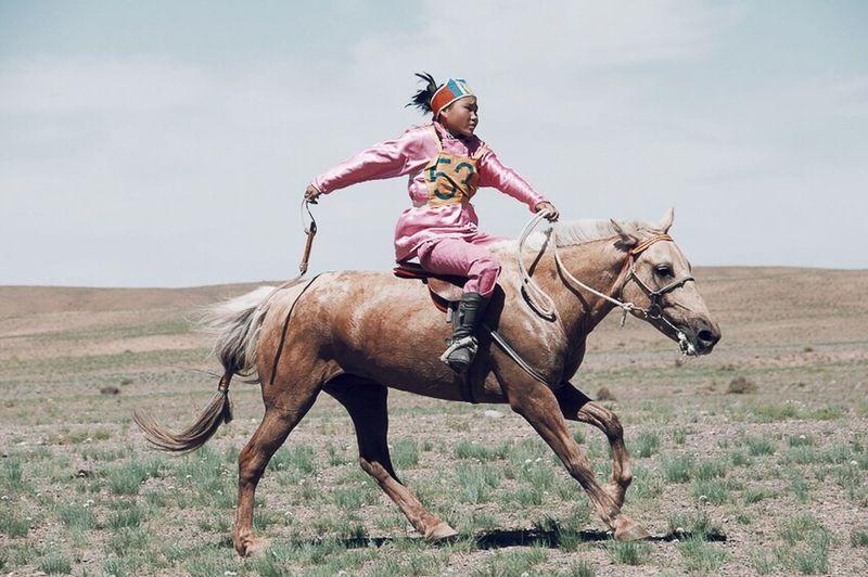 People And Places [UN]REALLY, MONGOLIA [5] 13 horses every human being, so I was told. Mongolia, a most uninhabited country, is sparsely occupied by horses, more than by human beings. Mongolians are born and raised with their horses: riding a horse is something ingrained, innate and cultivated at the same time. A lifestyle, timeless, and lasting. (In this photograph, a girl competing during the children's Naadam, Наадам, Games in Mongolian language. Women have been admitted to compete only recently). [IR]REALMENTE, MONGOLIA [5] 13 cavalli ogni essere umano, così mi raccontavano. La Mongolia, un paese praticamente disabitato, è occupato da cavalli più che da esseri umani. I mongoli nascono e crescono con i loro cavalli: andare a cavallo è qualcosa di connaturato, innato e coltivato allo stesso tempo. Uno stile di vita, senza tempo, che permane. (In questa fotografia, una bambina gareggia durante il Naadam, Наадам, Giochi in lingua mongola, riservato ai bambini. Le donne sono state ammesse a gareggiare solo di recente) By Claudia Ioan © Horse Riding Outdoors ASIA Mongolia Naadam People Travel Destinations Landscape VSCO Vscocam Nikon EyeEm Gallery The Roll Miles Away Women Around The World The Great Outdoors - 2017 EyeEm Awards