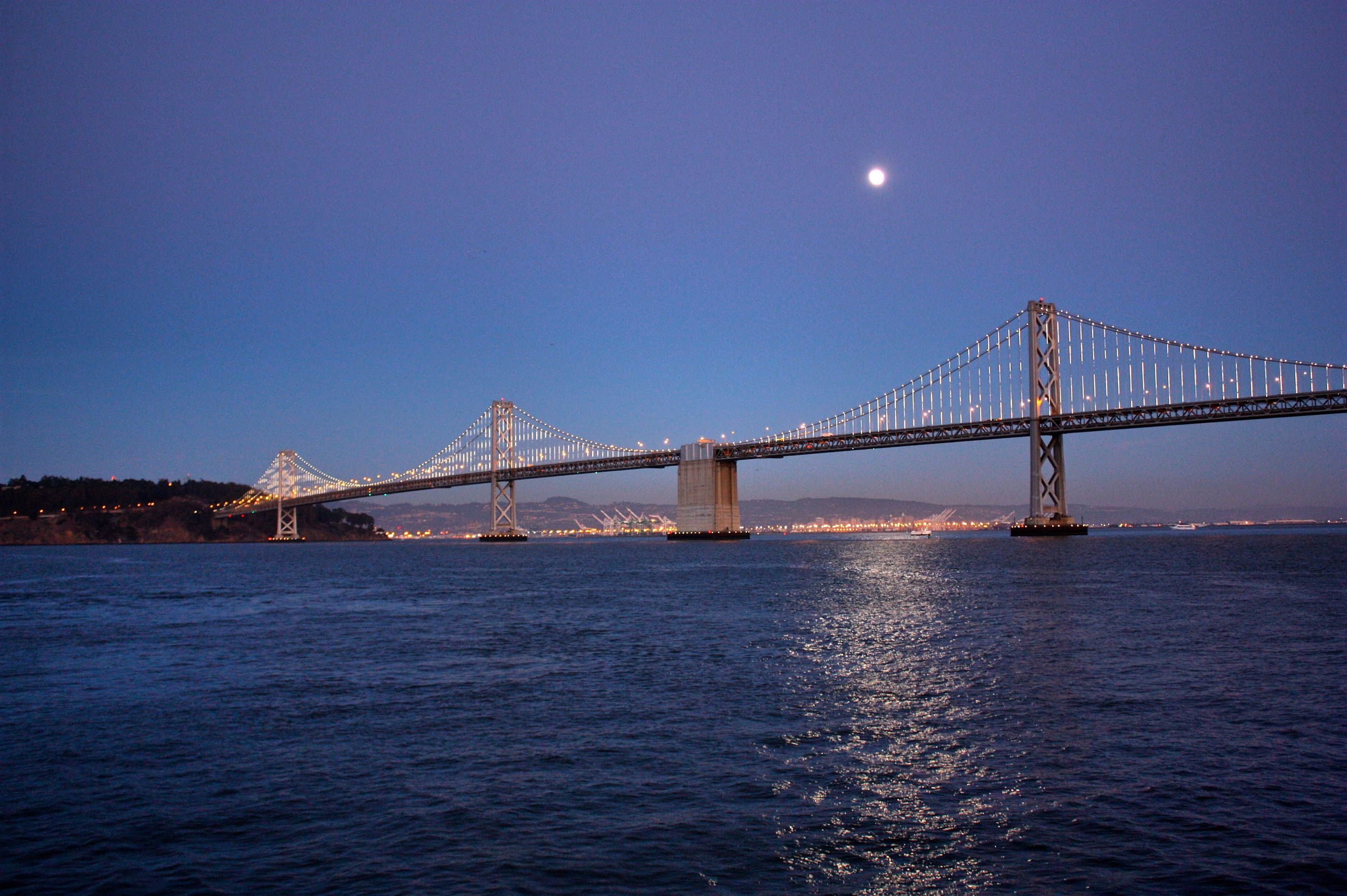connection, water, architecture, built structure, bridge - man made structure, waterfront, engineering, sea, suspension bridge, bridge, illuminated, clear sky, river, night, blue, copy space, transportation, rippled, sky, travel destinations