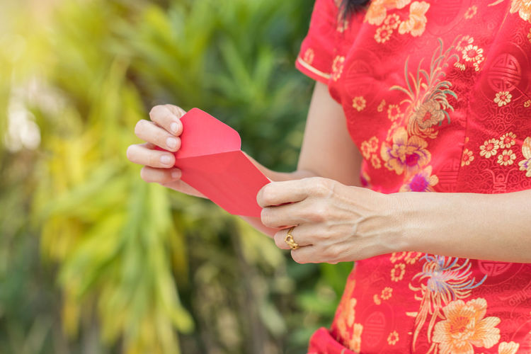 Midsection of woman holding red envelope