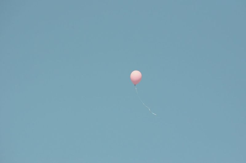 Low Angle View Of Peach Helium Balloon Flying In Clear Blue Sky