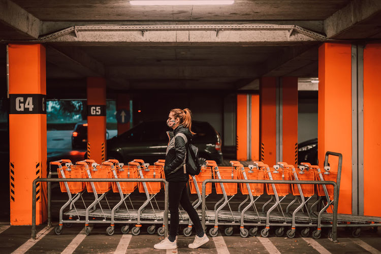 Full length portrait of woman standing in shopping cart