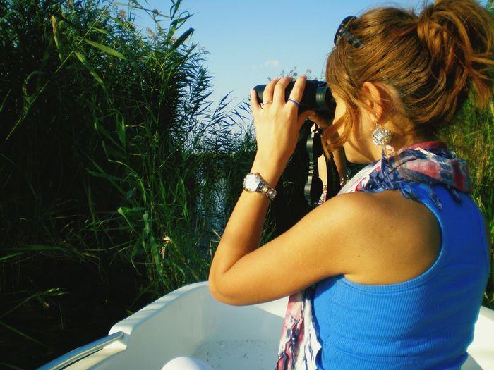 Side view of woman looking through binoculars