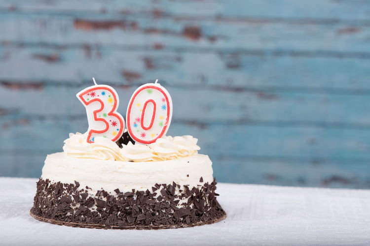 Number 30 candle on birthday cake over table against wall