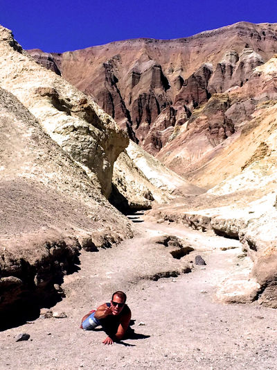 Man crawling on dirt road amidst rock formations during sunny day
