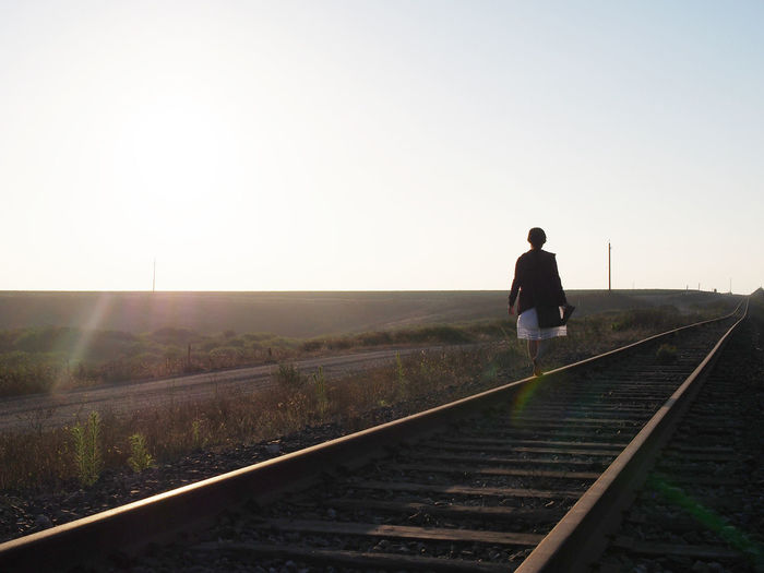 Rear view of woman walking on railroad track