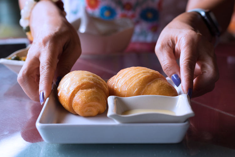 Asian  Breakfast Chinese Food Close-up Croissant Day Focus On Foreground Food Food And Drink Freshness Fried Buns Human Body Part Human Hand Indoors  Lifestyles Meals One Person Plate Ready-to-eat Real People Serving Dish Table