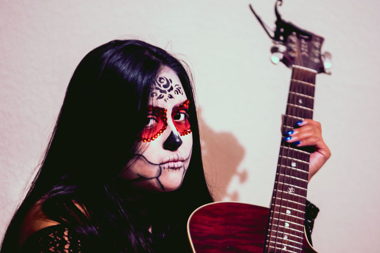 Close-Up Portrait Of Young Woman With Face Paint Holding Guitar At Home