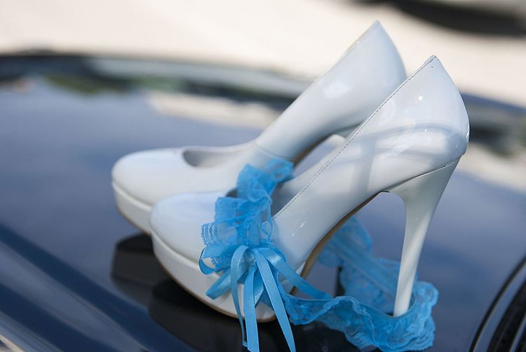 Close-up of high heels shoes with garter on car hood