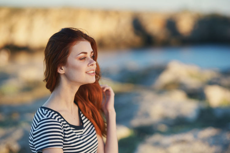 Young woman looking away while standing at shore