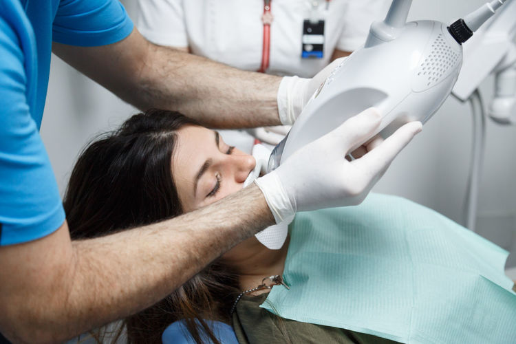 Young woman receiving a teeth whitening treatment at a dentist. Dental Dentist Electronic Hygiene Woman Brunette Caucasian Client Clinic Equipment Girl Health Healthcare And Medicine Instrument Medical Patient Procedure Professional Smile Technique Technology Teeth Treatment White Whitening