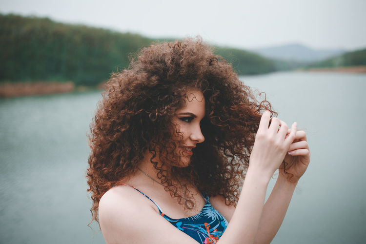 Young woman with curly hair standing against lake