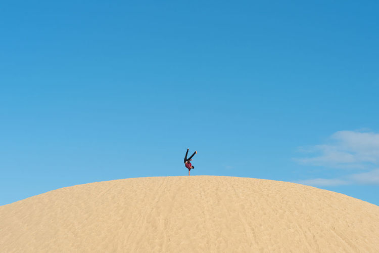 Man doing handstand at desert against clear blue sky
