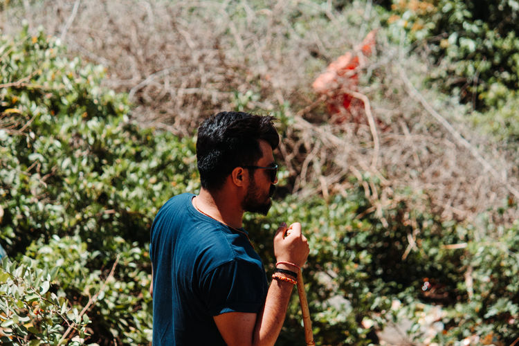 High angle view of young man looking away standing against plants