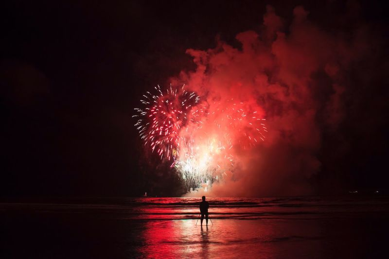 Silhouette man against firework exploding over shore at night