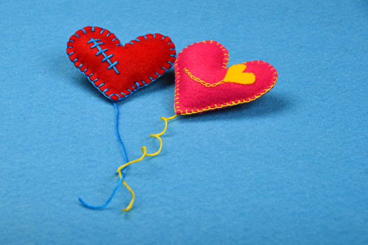 High angle view of heart shape decorations on blue fabric