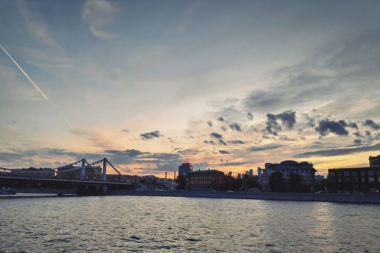 Bridge over river in city against sky during sunset