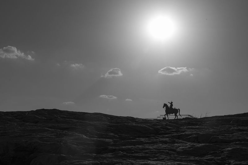 Silhouette people riding horse on beach against sky