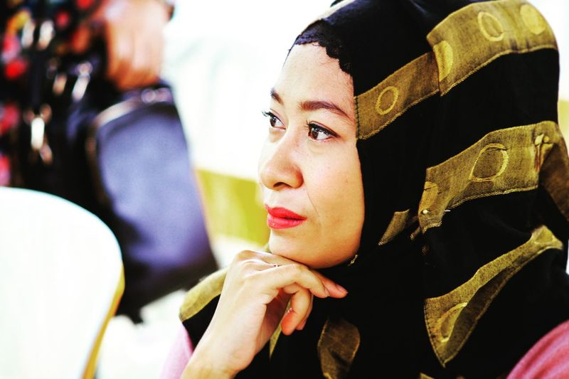 Close-up of thoughtful woman wearing striped hijab