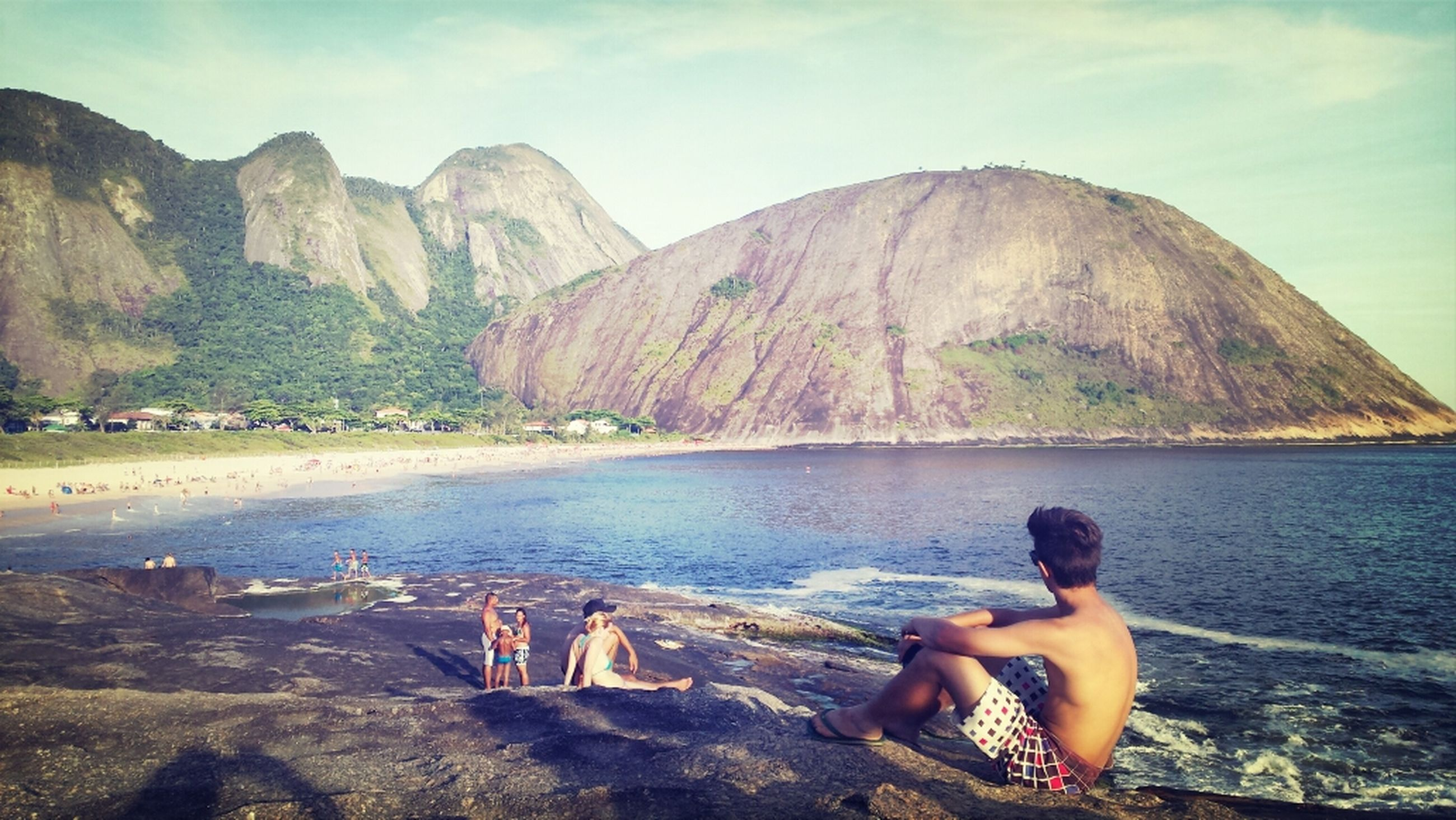 water, leisure activity, mountain, lifestyles, rock - object, vacations, sea, scenics, beauty in nature, tranquility, person, tranquil scene, nature, sky, relaxation, beach, men, sitting