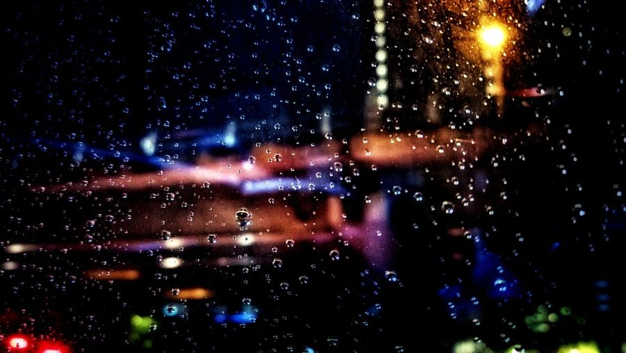 Raindrops on glass window at night