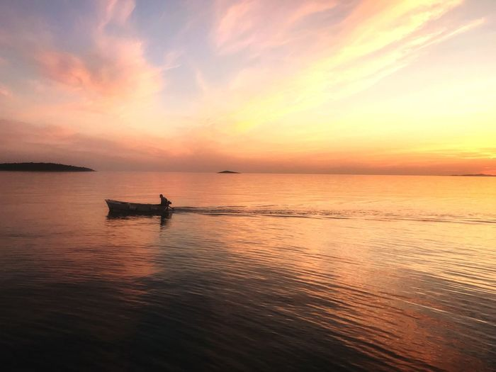 Fishermen in boat at the sea during sundown Fisherman Boat Sunset Sunset Sky Water Beauty In Nature Sea Scenics - Nature Orange Color Tranquility Horizon Horizon Over Water Tranquil Scene Idyllic Cloud - Sky Nautical Vessel Outdoors Non-urban Scene Reflection Transportation Nature