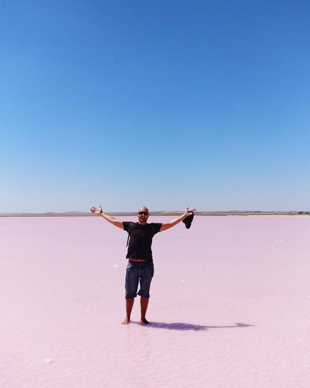 Portrait of man with arms outstretched standing at lake bumbunga against clear sky