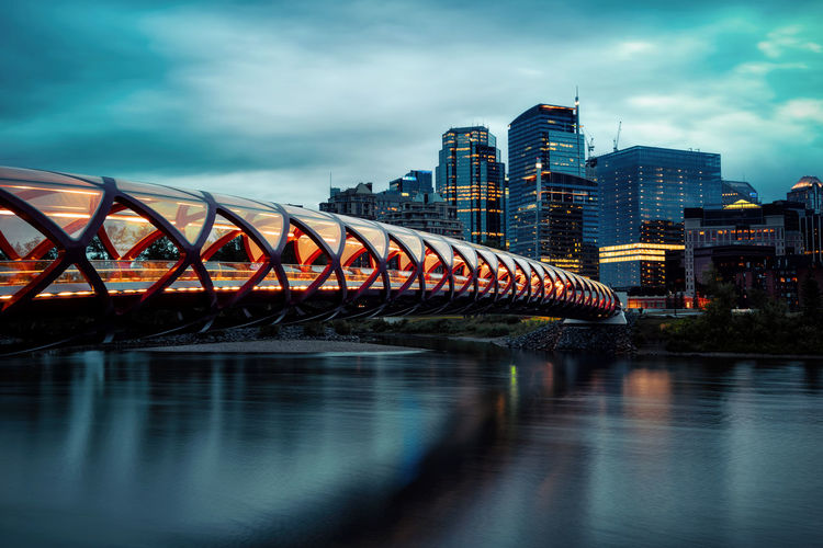 Illuminated bridge over river by buildings against sky in city