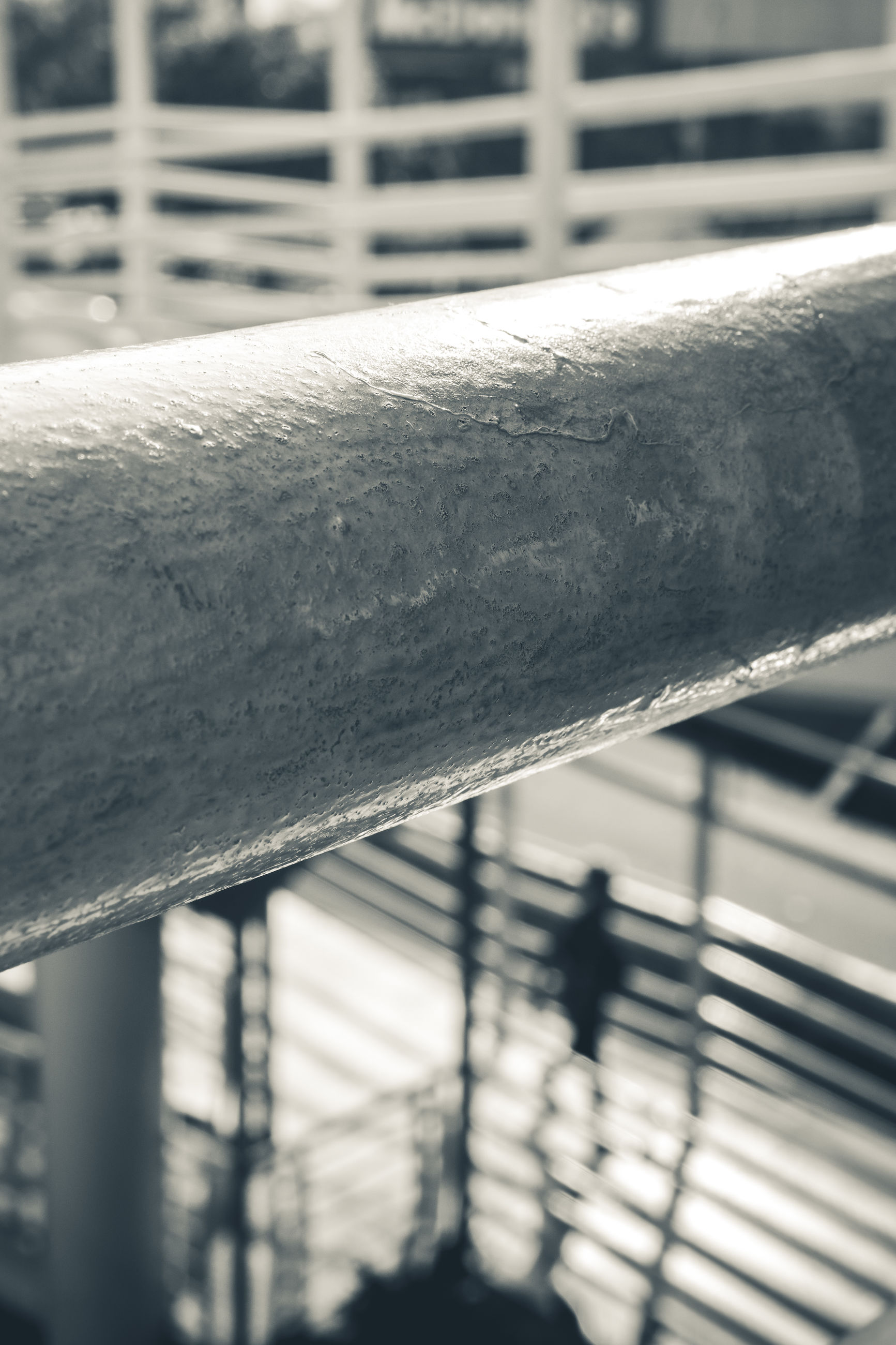 focus on foreground, metal, close-up, railing, no people, day, architecture, outdoors, pattern, sunlight, rod, built structure, nature, fence, safety, barrier, selective focus, connection, security, textured, iron, steel