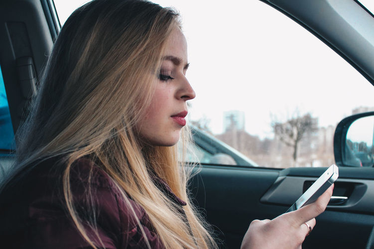 Woman looking away while sitting in car