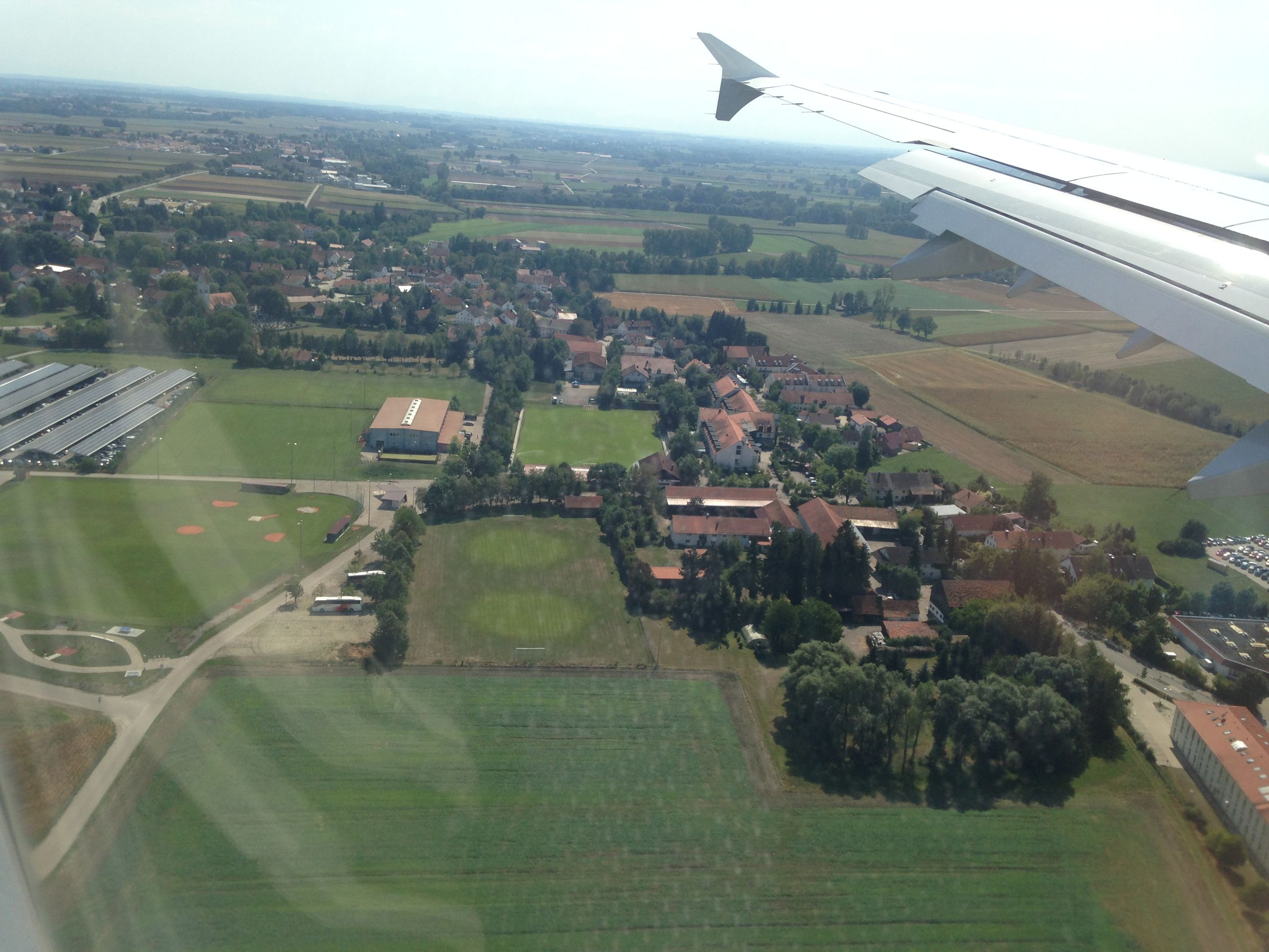 airplane, flying, air vehicle, transportation, mode of transport, aircraft wing, landscape, aerial view, public transportation, mid-air, on the move, travel, part of, journey, cropped, field, rural scene, sky, nature, scenics