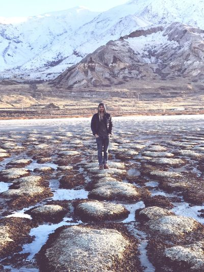 Man standing on field against snowcapped mountains