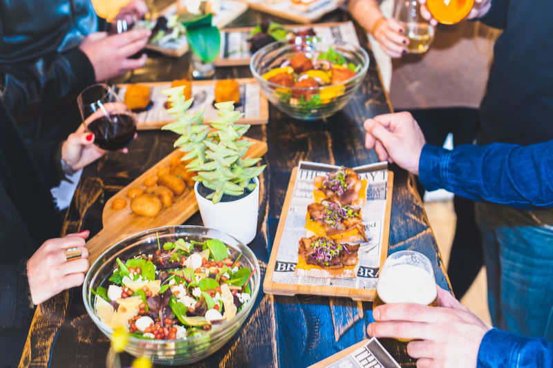 Midsection of friends with various food at table in restaurant