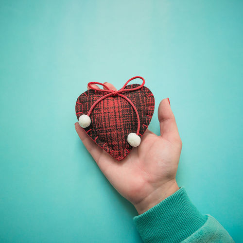 Close-up of hand holding heart shape decoration over turquoise background