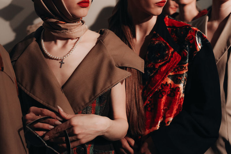 Cropped young russian models with red lips in a brown designer clothing posing on the backstage