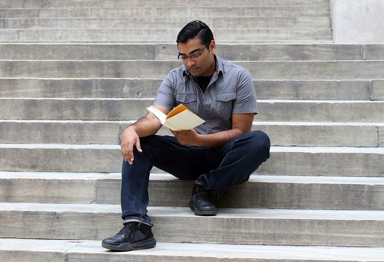 Low angle view of man reading book on steps