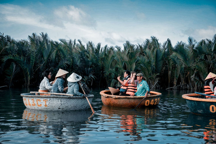 Panoramic view of people in boat against sky