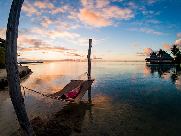 High angle view of woman relaxing on hammock in sea at sunset