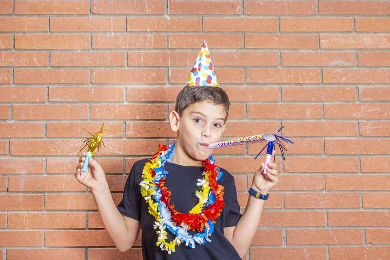 Portrait of boy wearing party equipment against brick wall