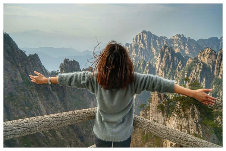 Rear View Of Woman With Arms Outstretched At Observation Point Against Mountains