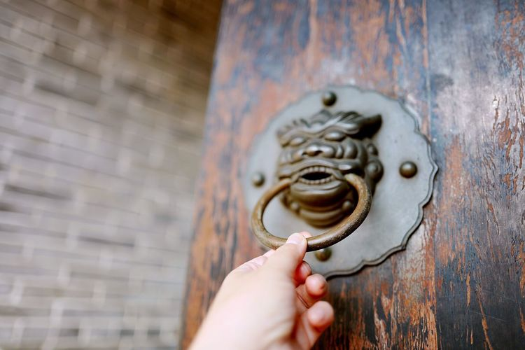Cropped hand of person holding door knocker