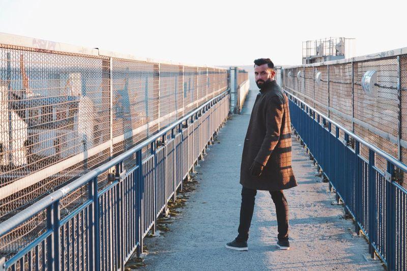 Man standing on footbridge against clear sky