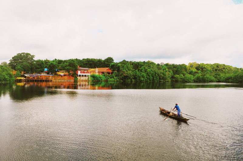 High angle view of man rowing fishing boat on lake