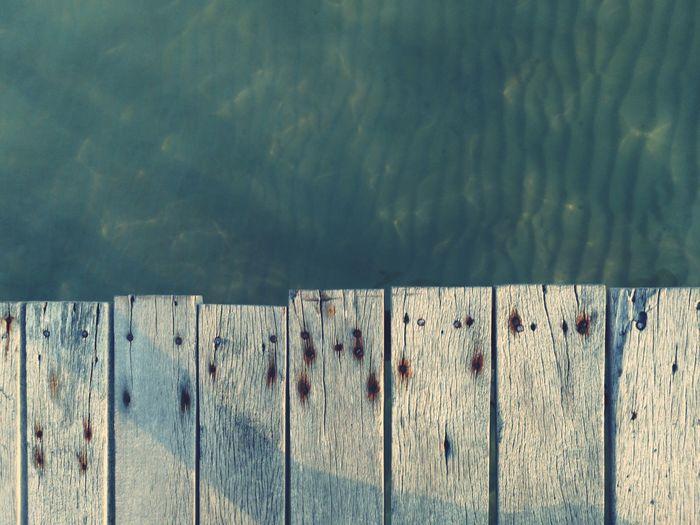 Close-up of wooden fence on pier against lake