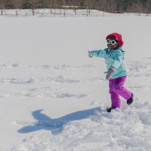 Full length of girl walking on snowy field during winter