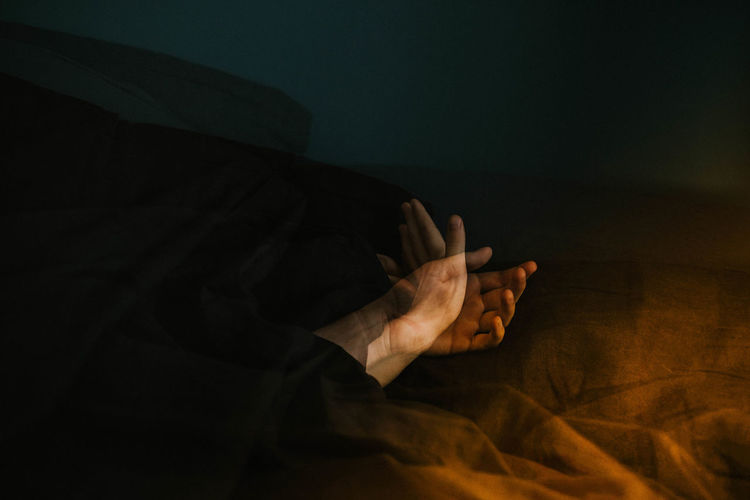 Double exposure image of textile and hands at night