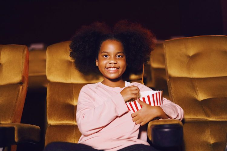Girl holding food while sitting on chair in movie theater