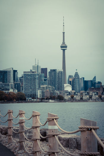 Autumn CN Tower Lake Ontario Skyline Architecture Building Exterior Buildings Built Structure City Cityscape Clear Sky Day Desaturated Fence Grey Sky Modern No People Outdoors Sky Skyscraper Tall Tower Travel Destinations Urban Skyline Water Colour Your Horizn Stories From The City